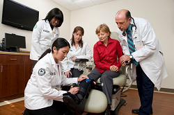 Clinical image of a physician and students helping a female patient with an injured leg