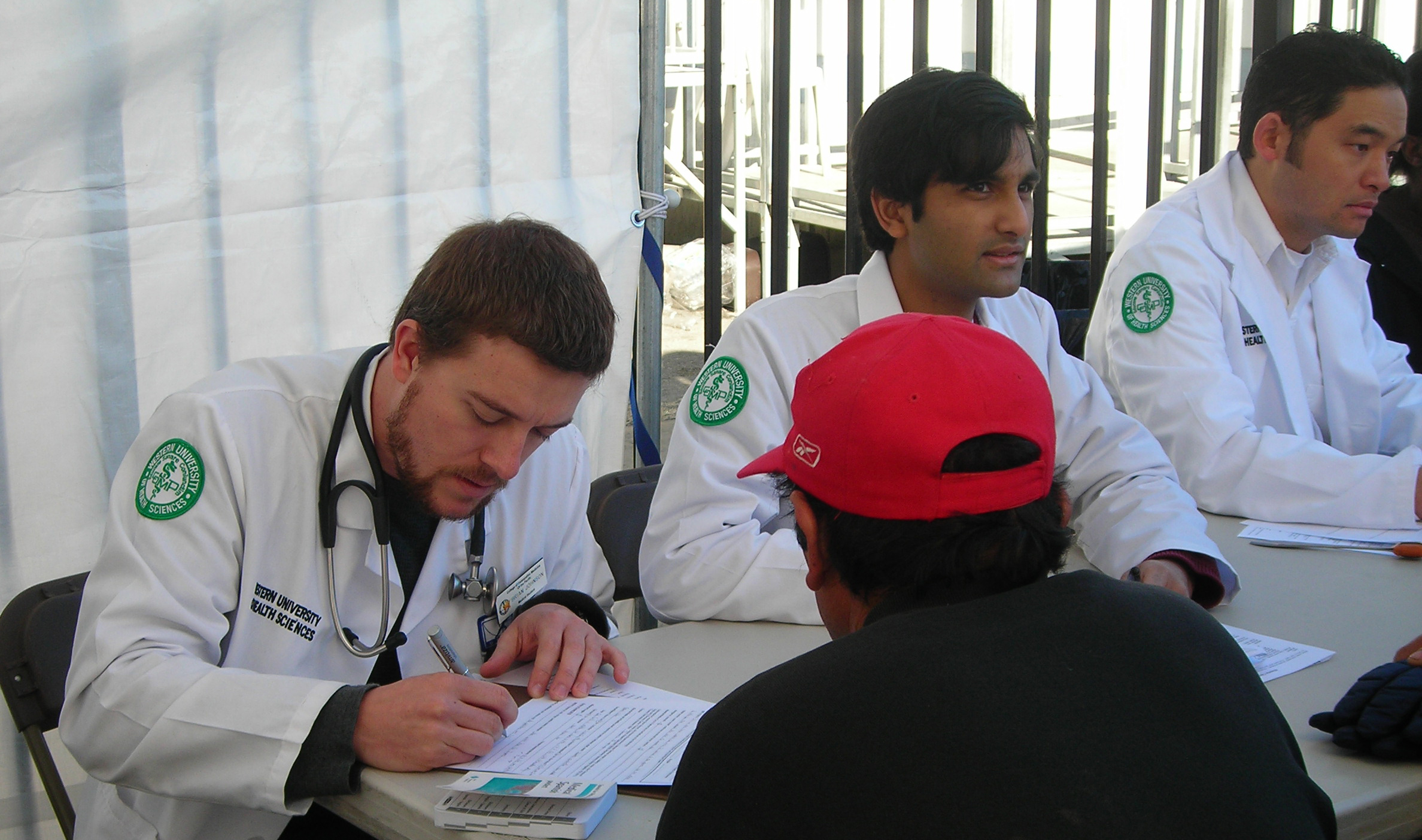 Faculty and students in white coats with a patient during an outdoor event.