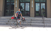 Student William Chen stands in front of building with bicycle