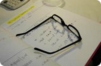 Reading glasses placed on an open lab notebook